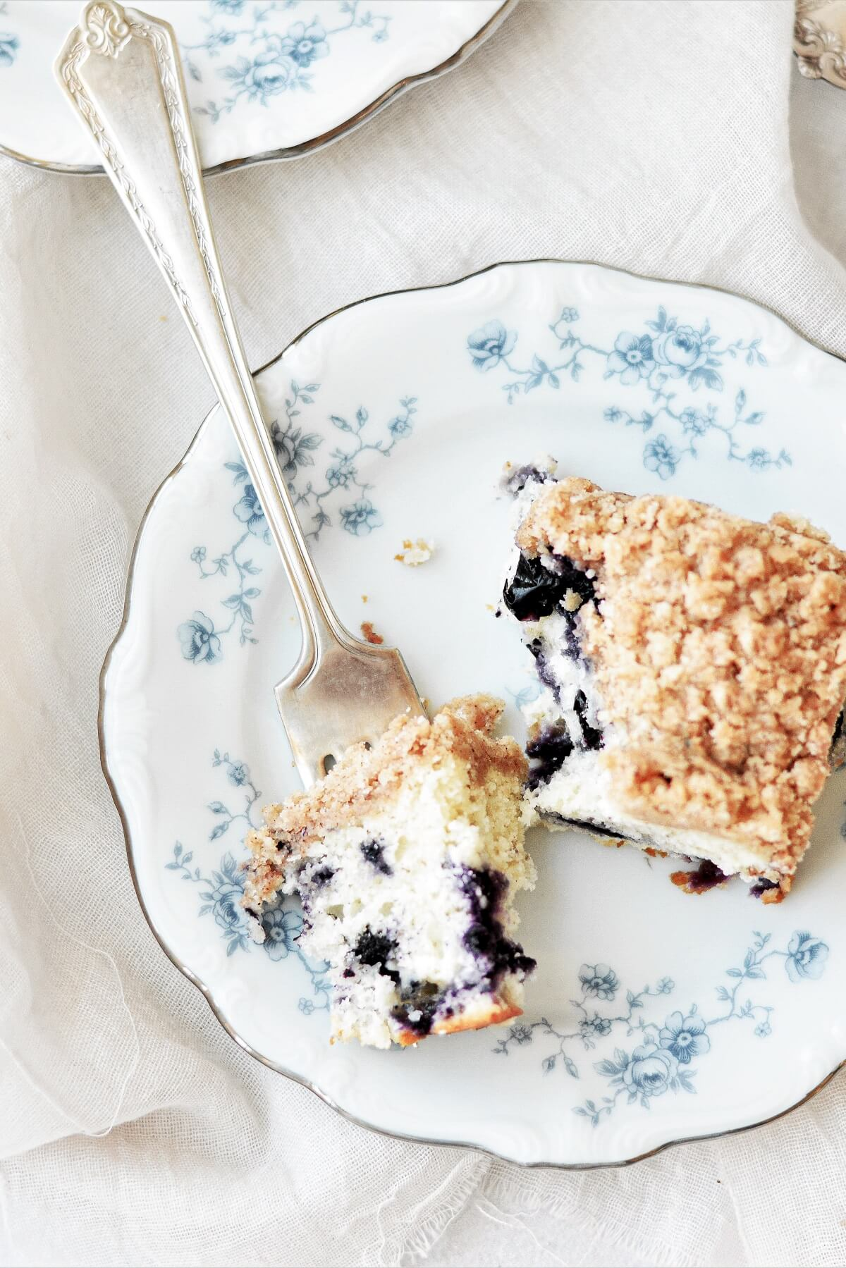 A piece of blueberry buckle coffee cake with a bite taken.