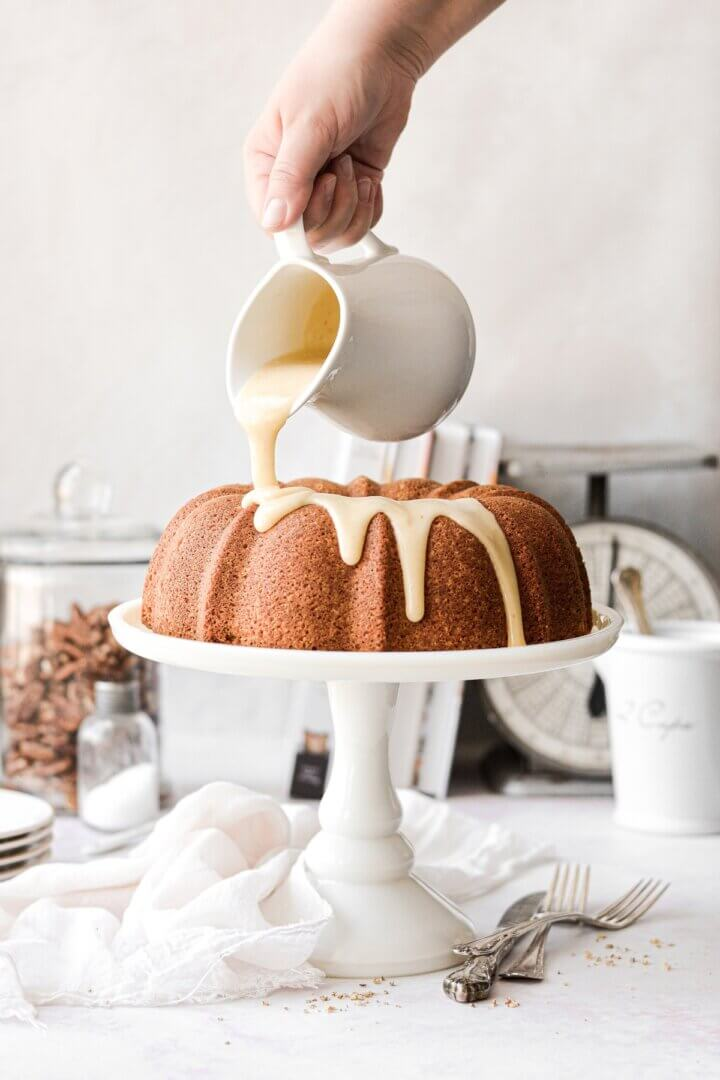 Butter pecan pound cake on a white cake stand, with bourbon icing being poured on top.