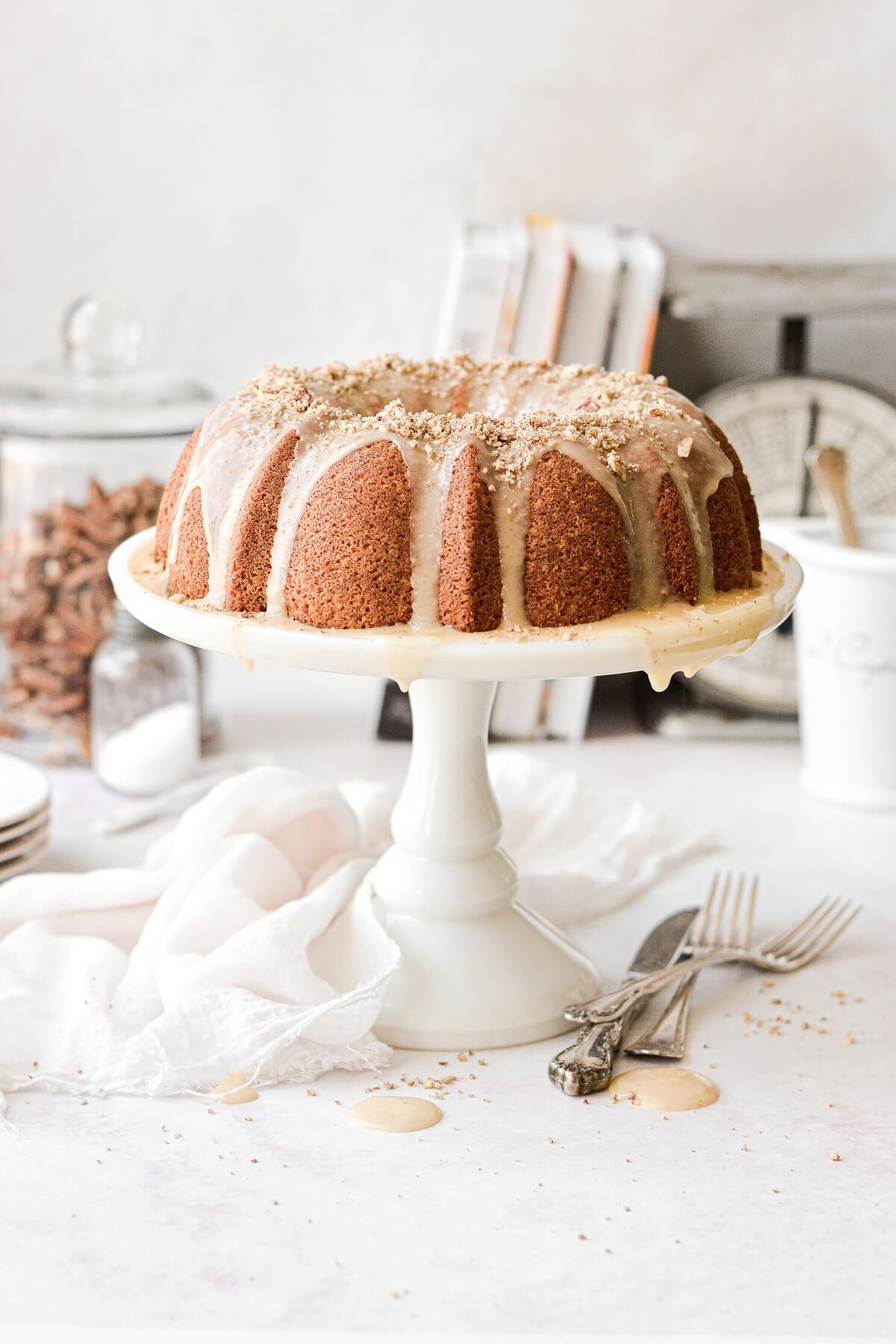 Butter pecan pound cake on a white cake stand, with bourbon icing.