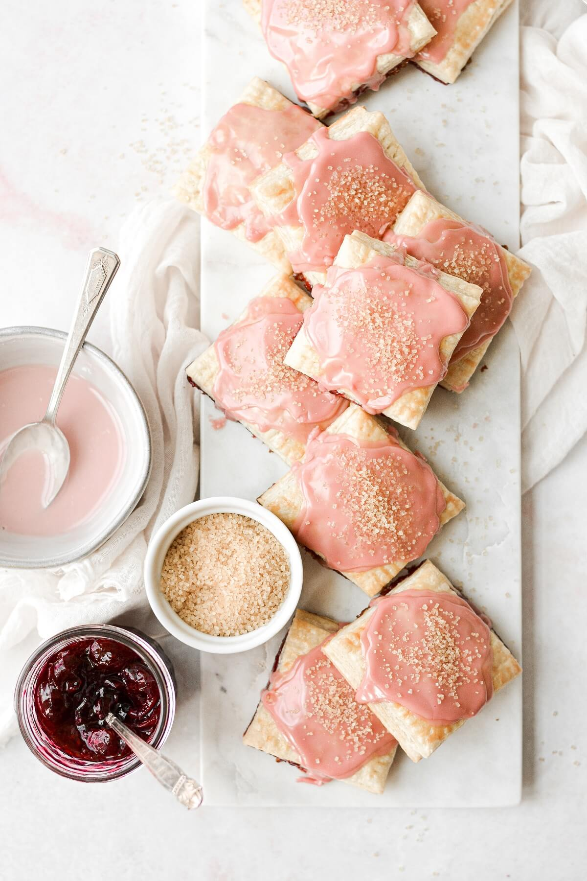 Homemade cherry pop tarts, arranged on a marble board, sprinkled with sugar.