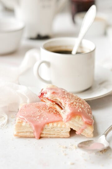 Homemade cherry pop tarts, next to a cup of coffee.