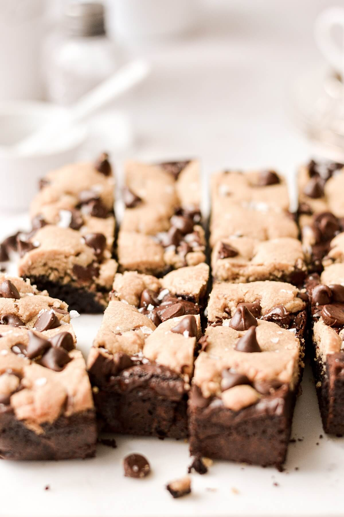 Chocolate chip cookie brownies arranged on a white marble board.