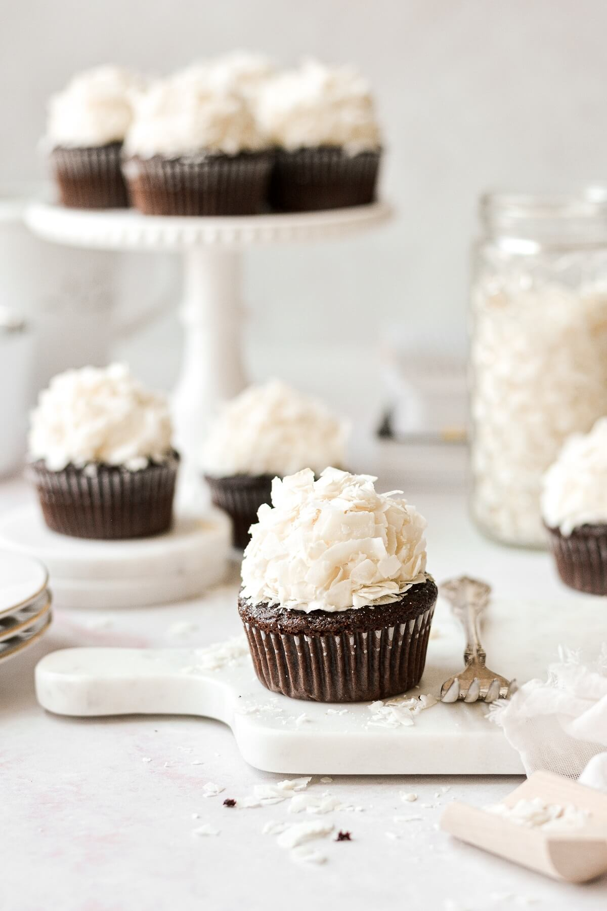 Chocolate coconut cupcakes on a marble board.