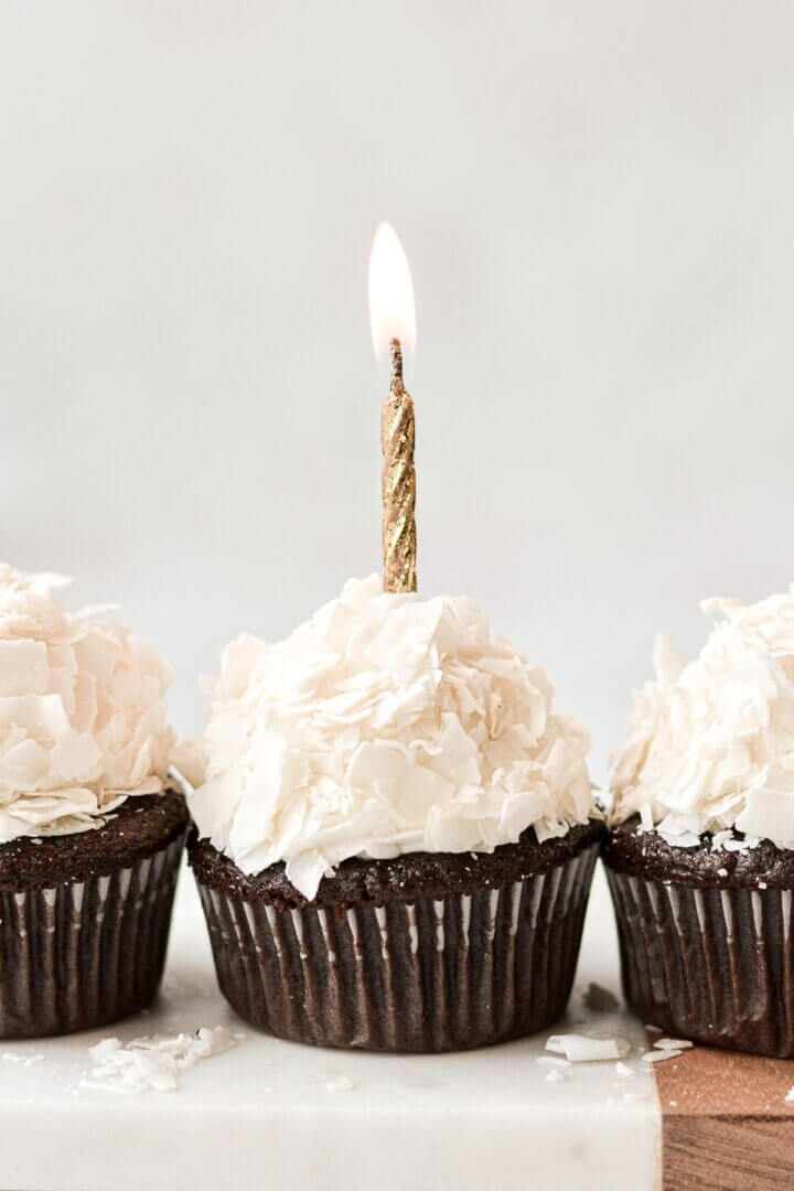 A chocolate cupcake with coconut frosting and a gold birthday candle.