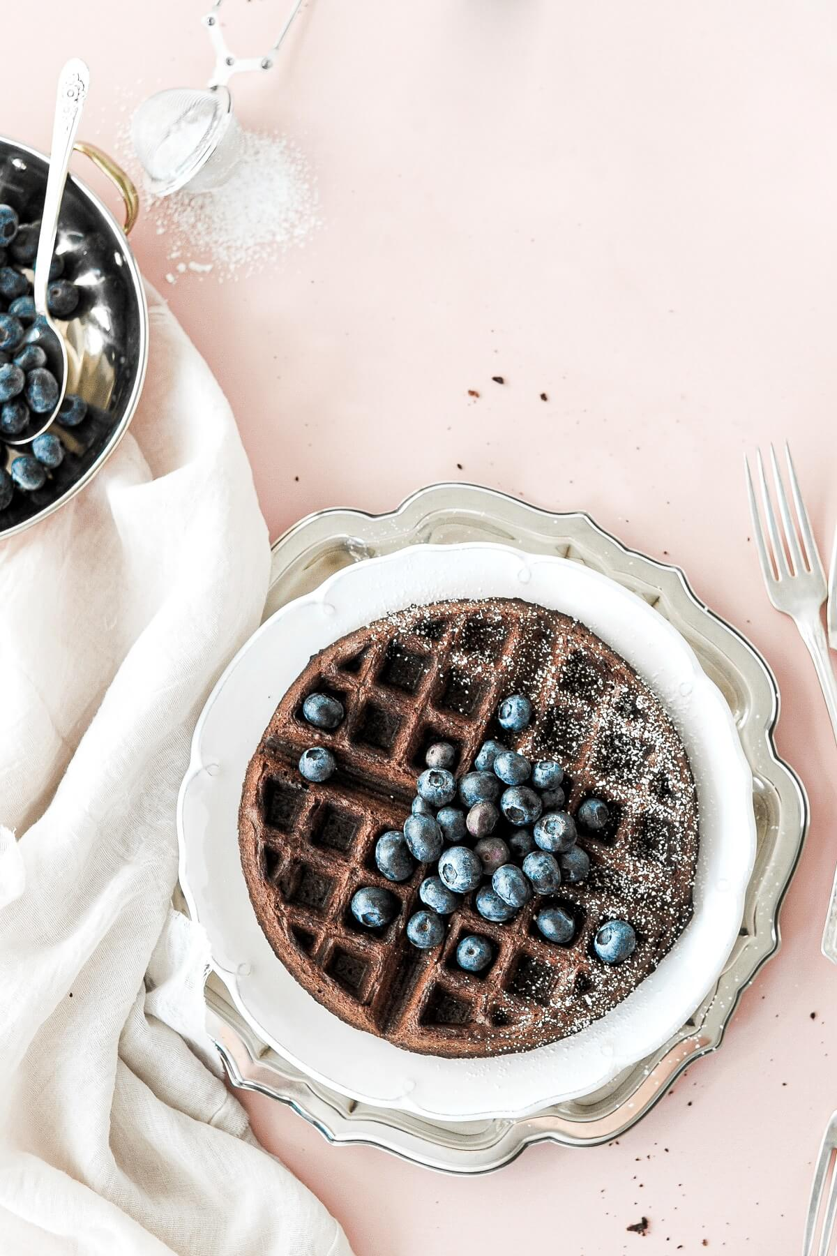 A chocolate waffle with blueberries and powdered sugar.