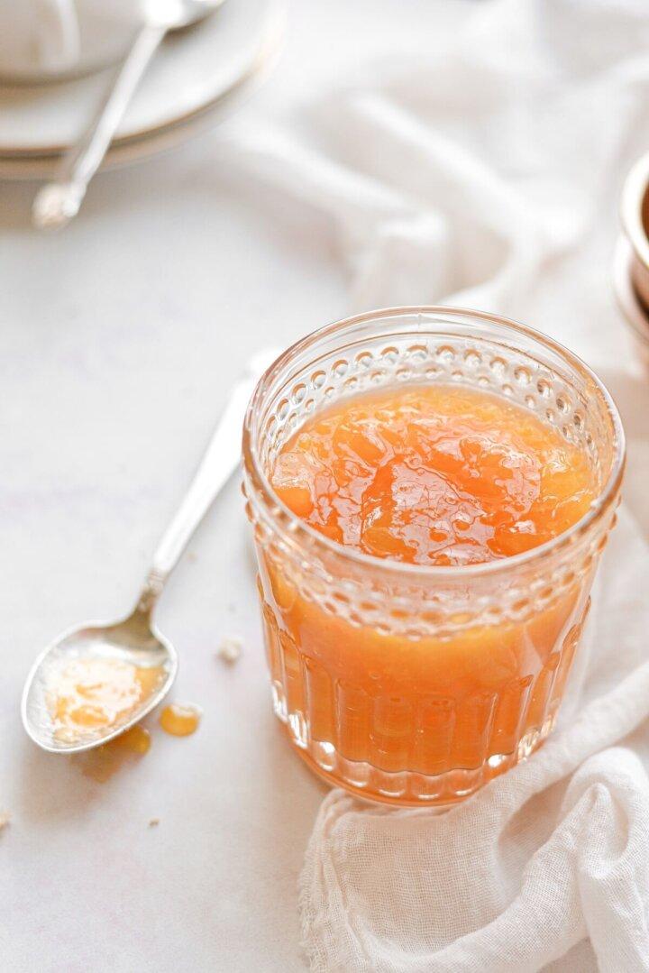 A glass jar of peach apricot jam.