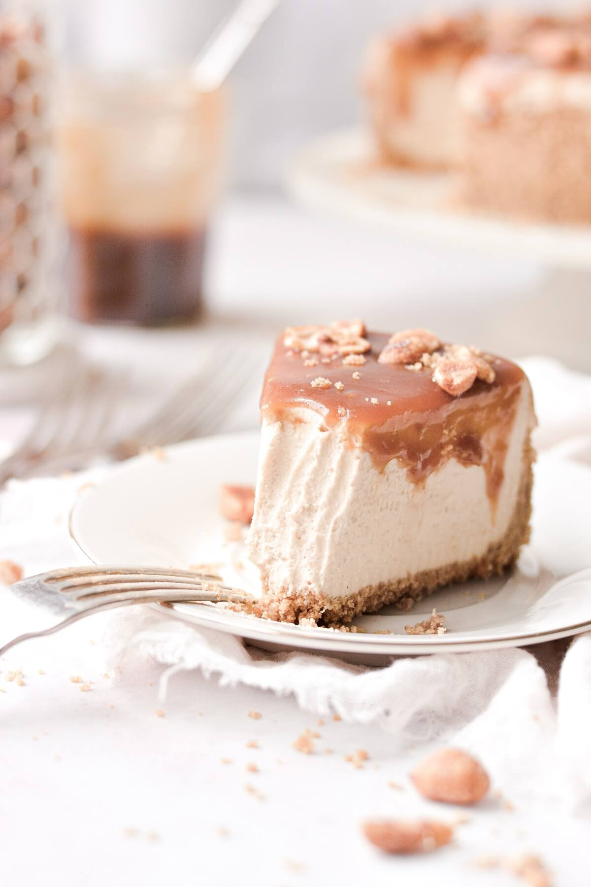 A slice of peanut butter cheesecake with a bite taken.