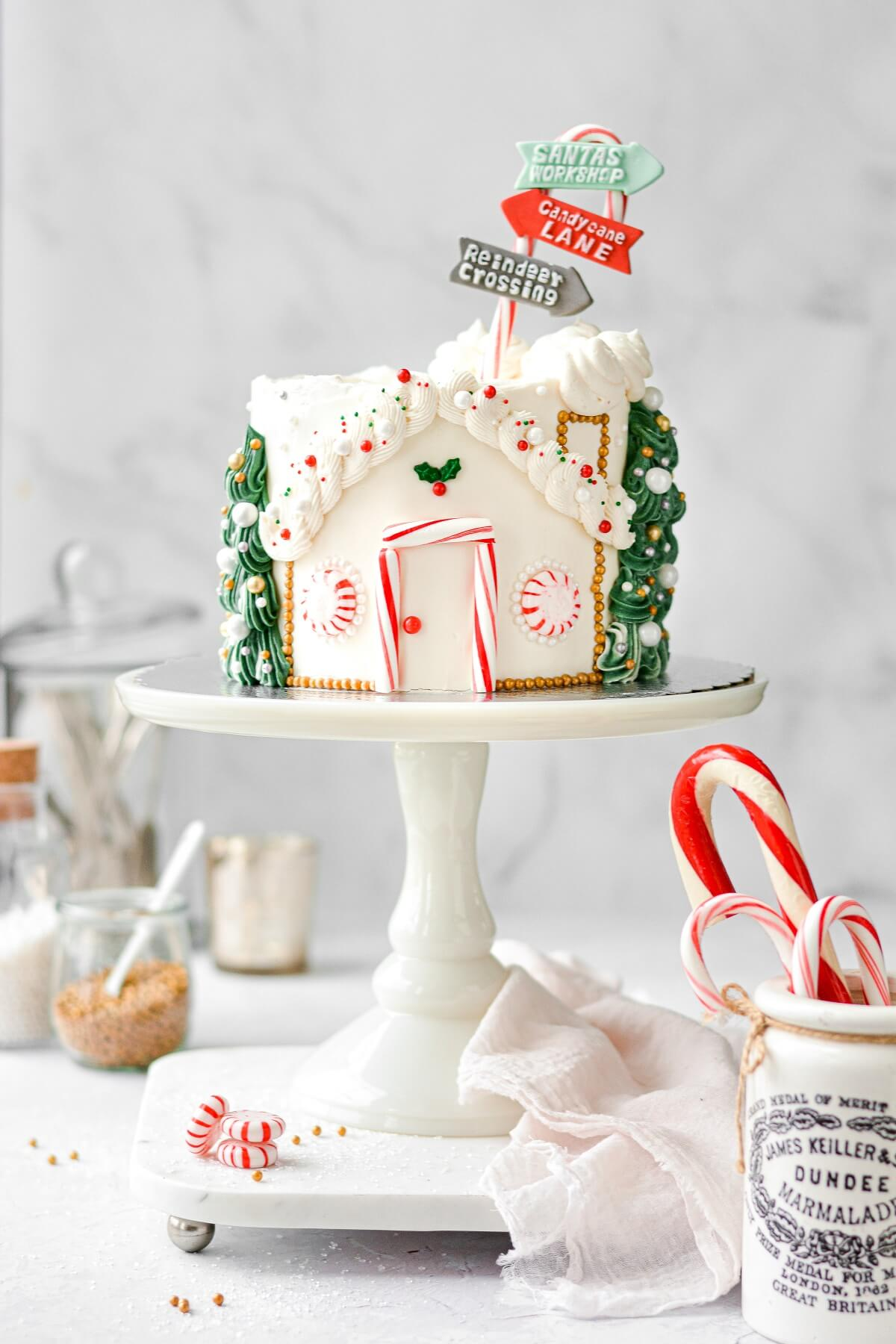 A Santa's Workshop Cake, with a candy door, buttercream trees, and a candy cane sign.