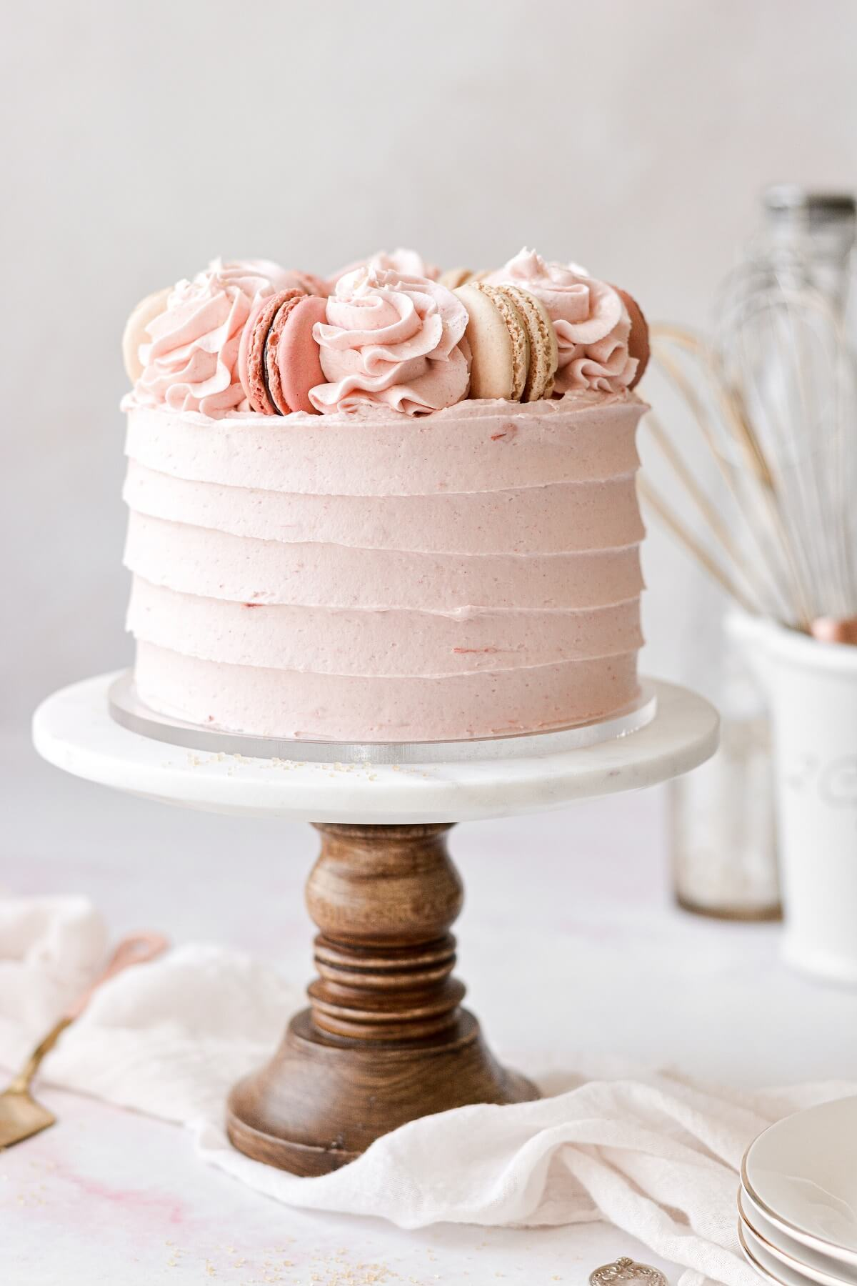 Strawberry almond cake with textured buttercream and macarons on top.