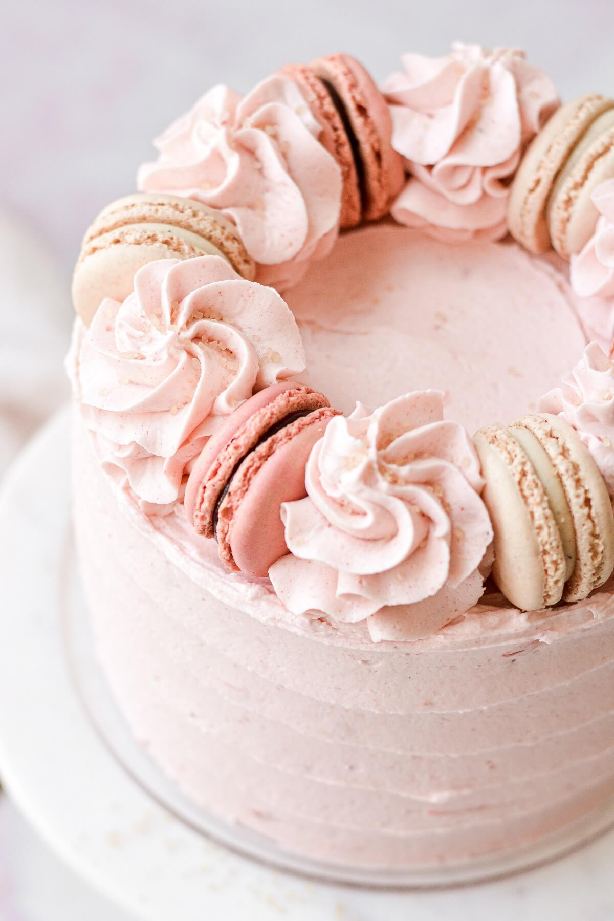 The top of a strawberry almond cake with buttercream swirls and macarons.
