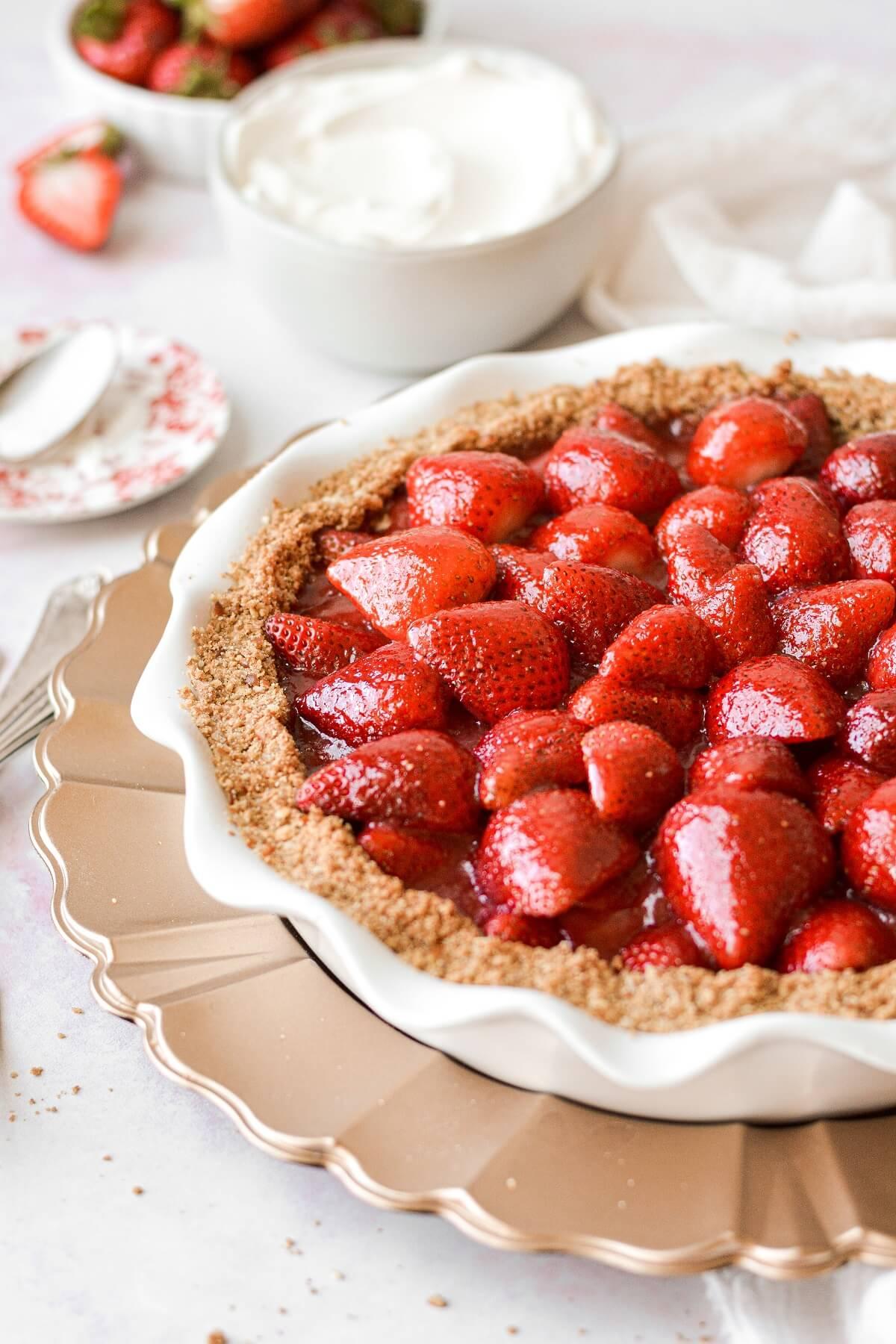Strawberry pretzel pie, next to a bowl of whipped cream.