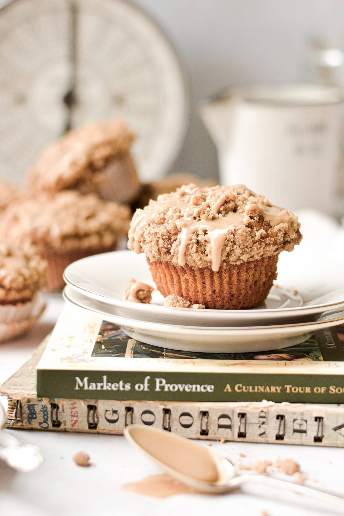 A sweet potato crumb muffin, on a stack of plates, sitting on a cookbook.