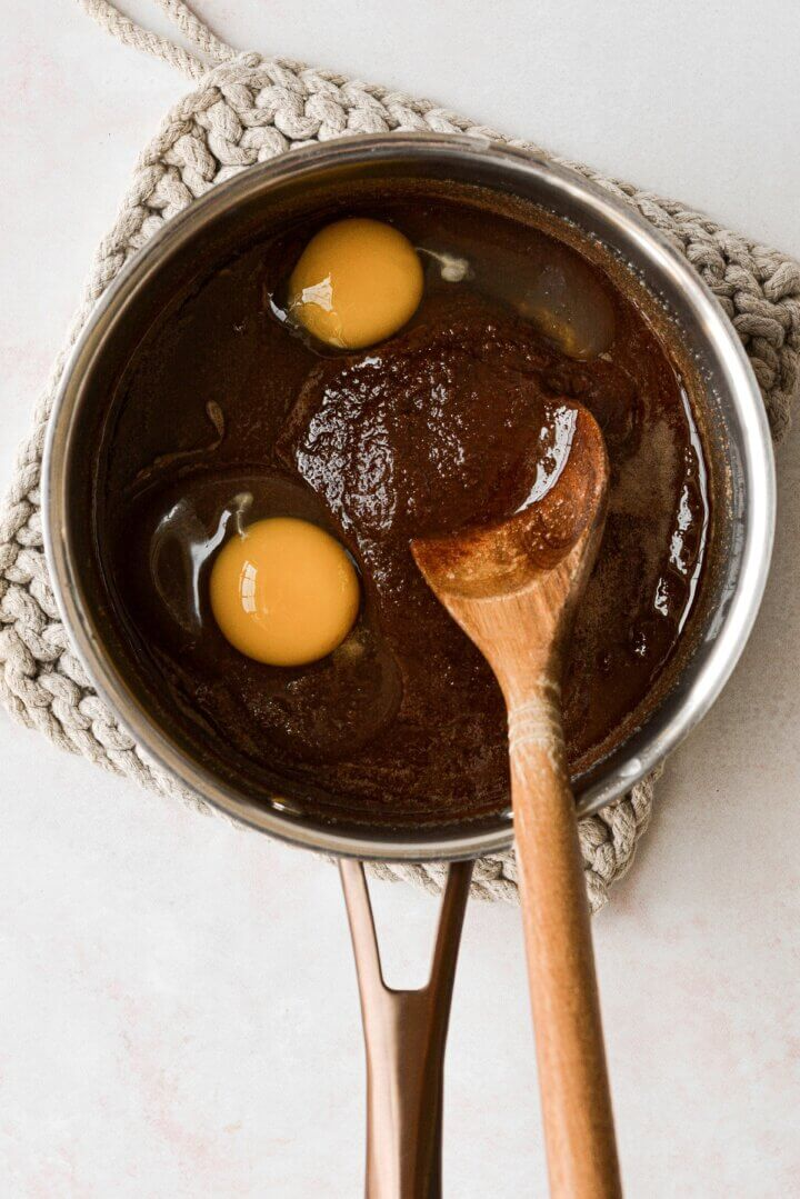 Stirring eggs into brownie batter.