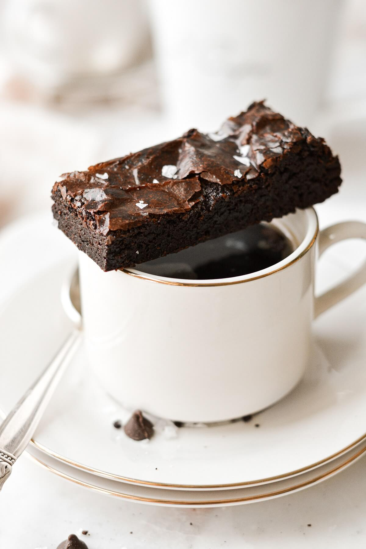 A fudge brownie sitting on top of a cup of coffee.