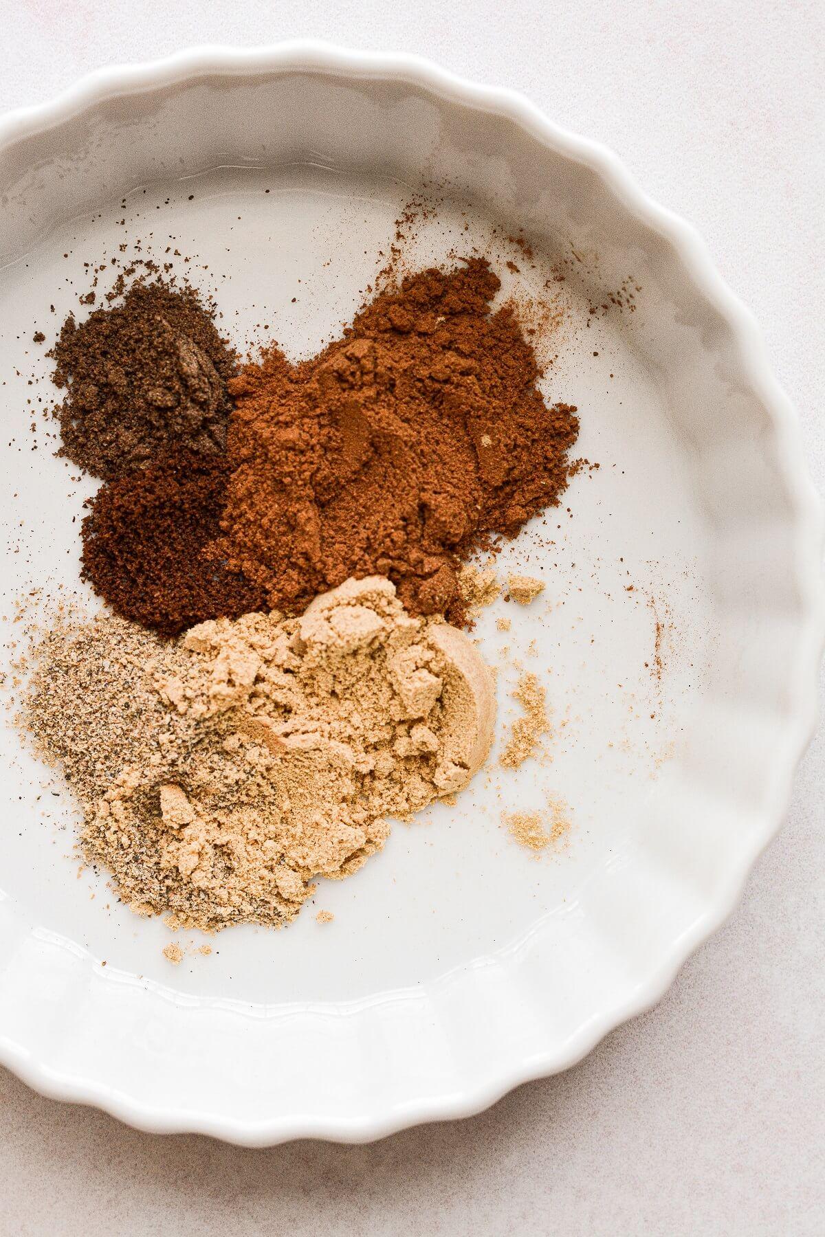 A blend of spices in a white ramekin.