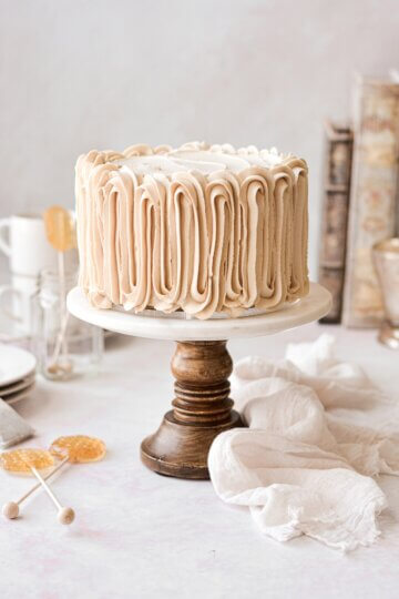 Chai tea spice cake with piped buttercream on a marble and wood cake stand.