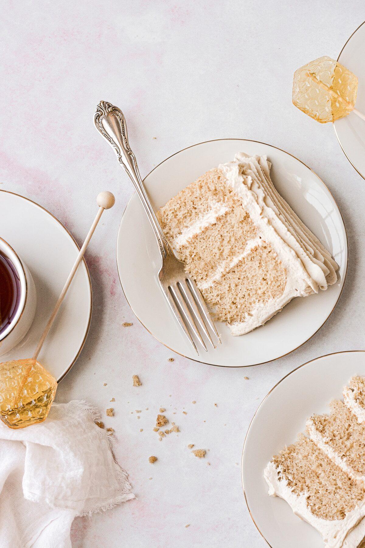 Slices of chai tea spice cake, next to cups of tea and honey stir sticks.