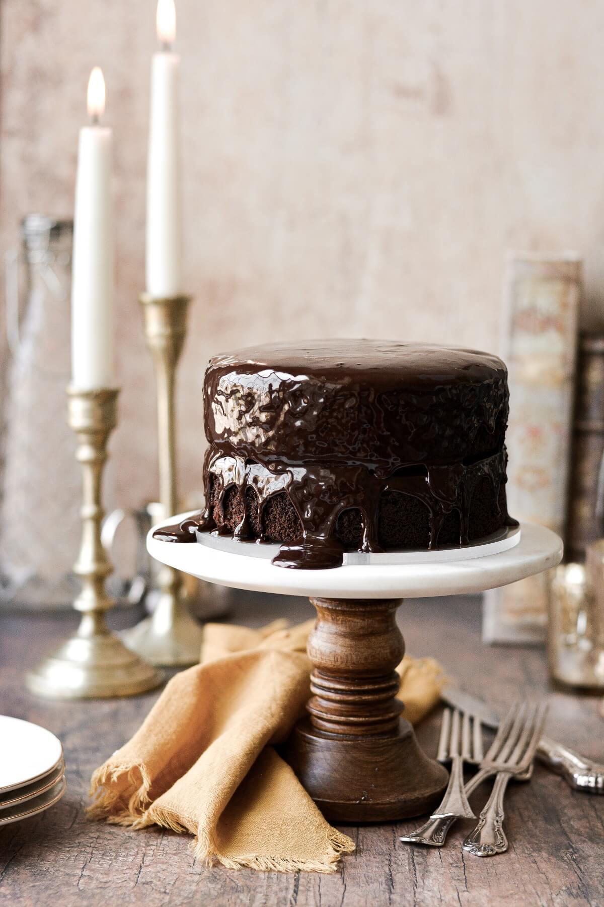 A chocolate fudge cake with ganache on a wood and marble cake stand.