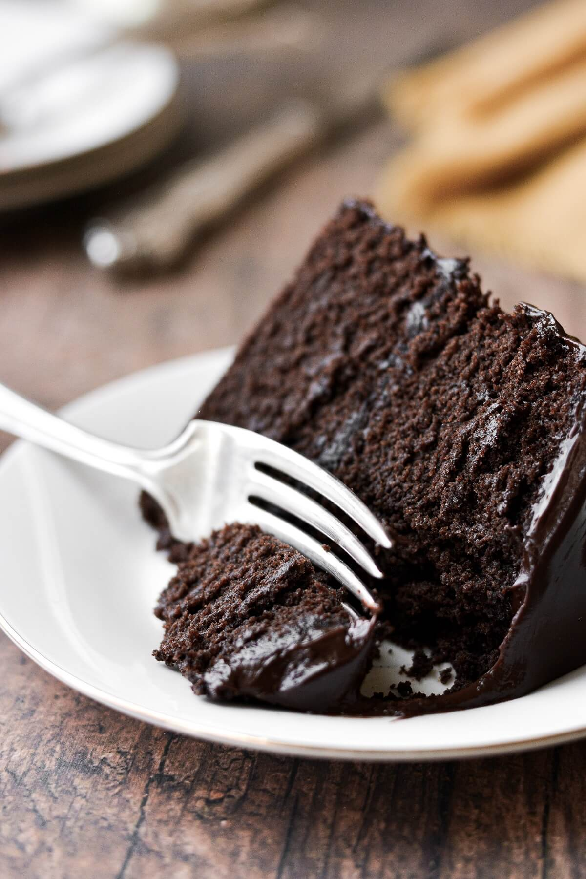 A slice of chocolate fudge cake with a bite taken.