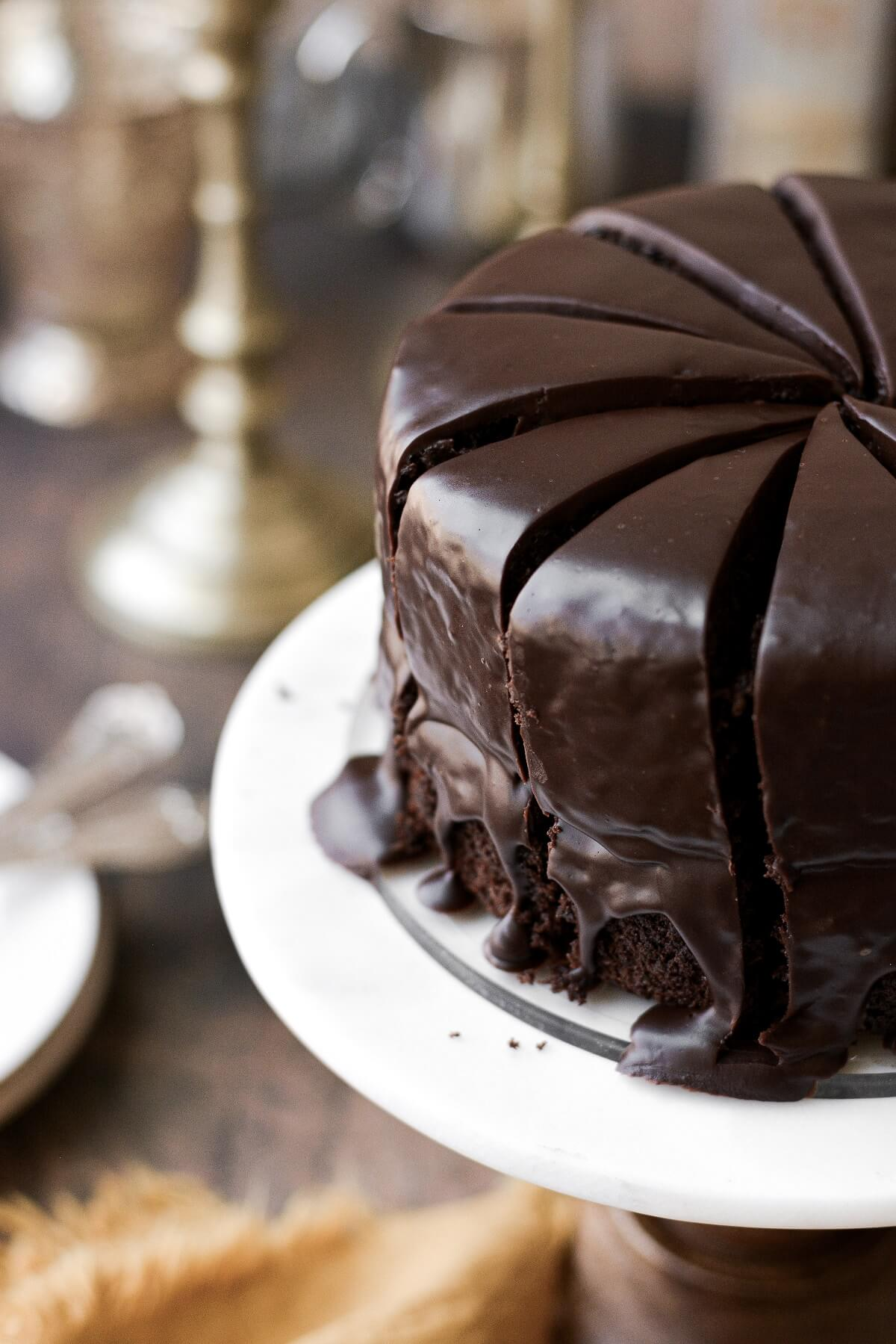 A chocolate fudge cake cut into slices on a cake stand.