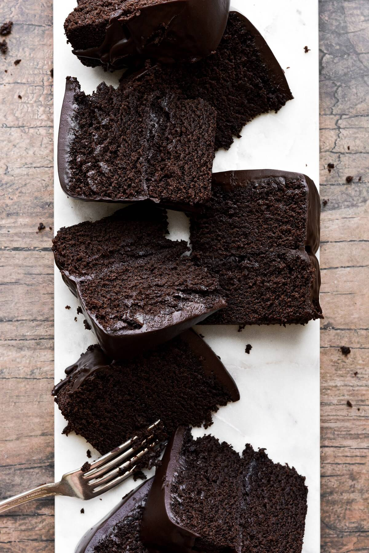 Slices of chocolate fudge cake on a white marble board.