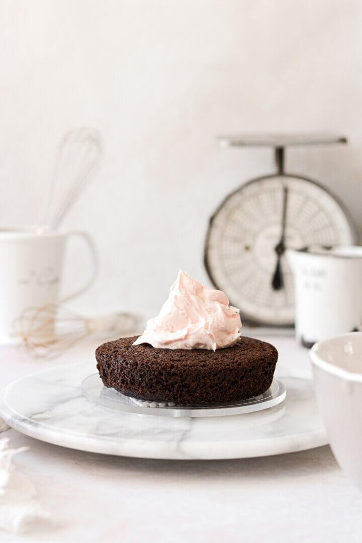 A layer of chocolate cake topped with a dollop of pink frosting.