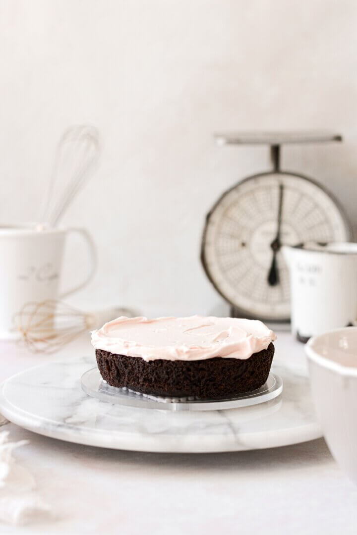 A layer of chocolate cake spread with pale pink frosting.