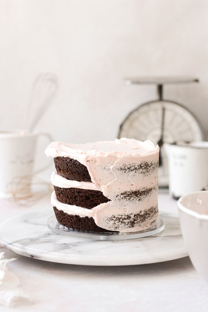 Demonstrating how to crumb coat a cake with layers of chocolate cake and pale pink buttercream.