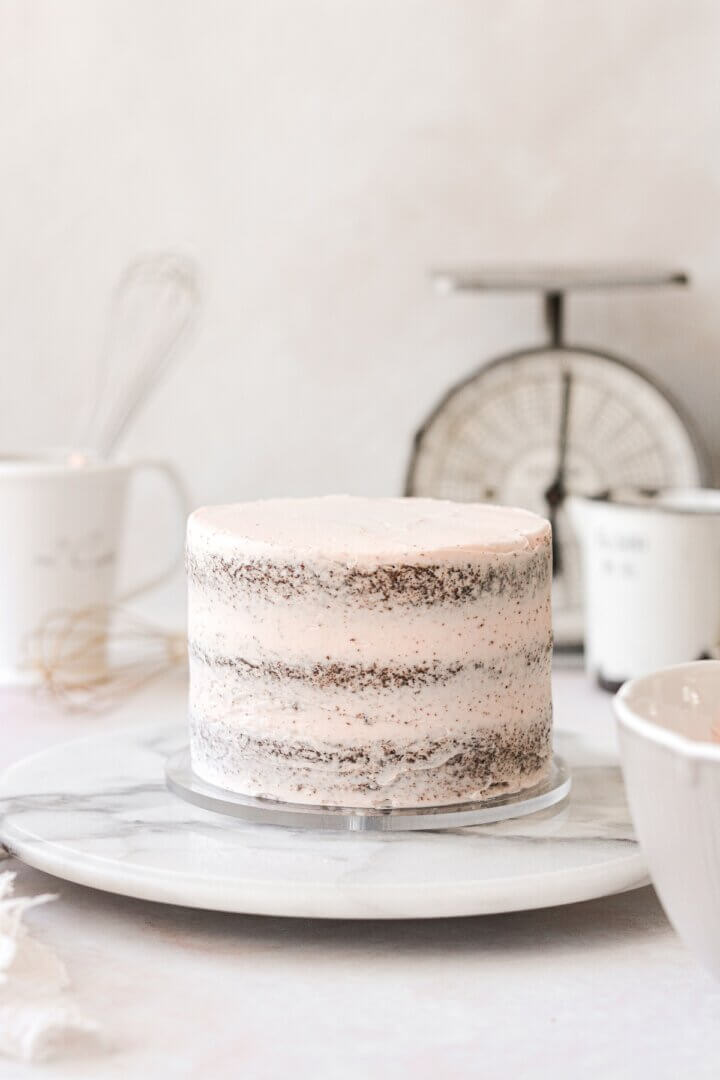 An assembled chocolate cake with a crumb coat in pale pink buttercream.