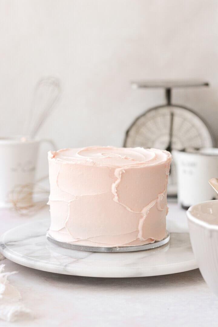 Pale pink buttercream swirled onto a layer cake.
