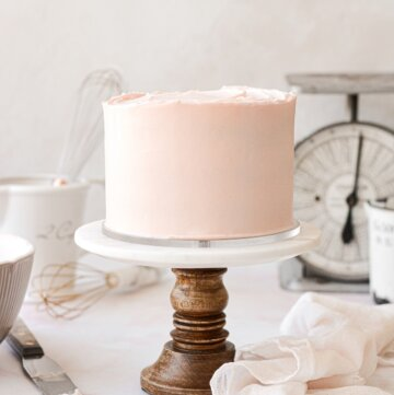 A pale pink frosted cake on a marble and wood cake stand.