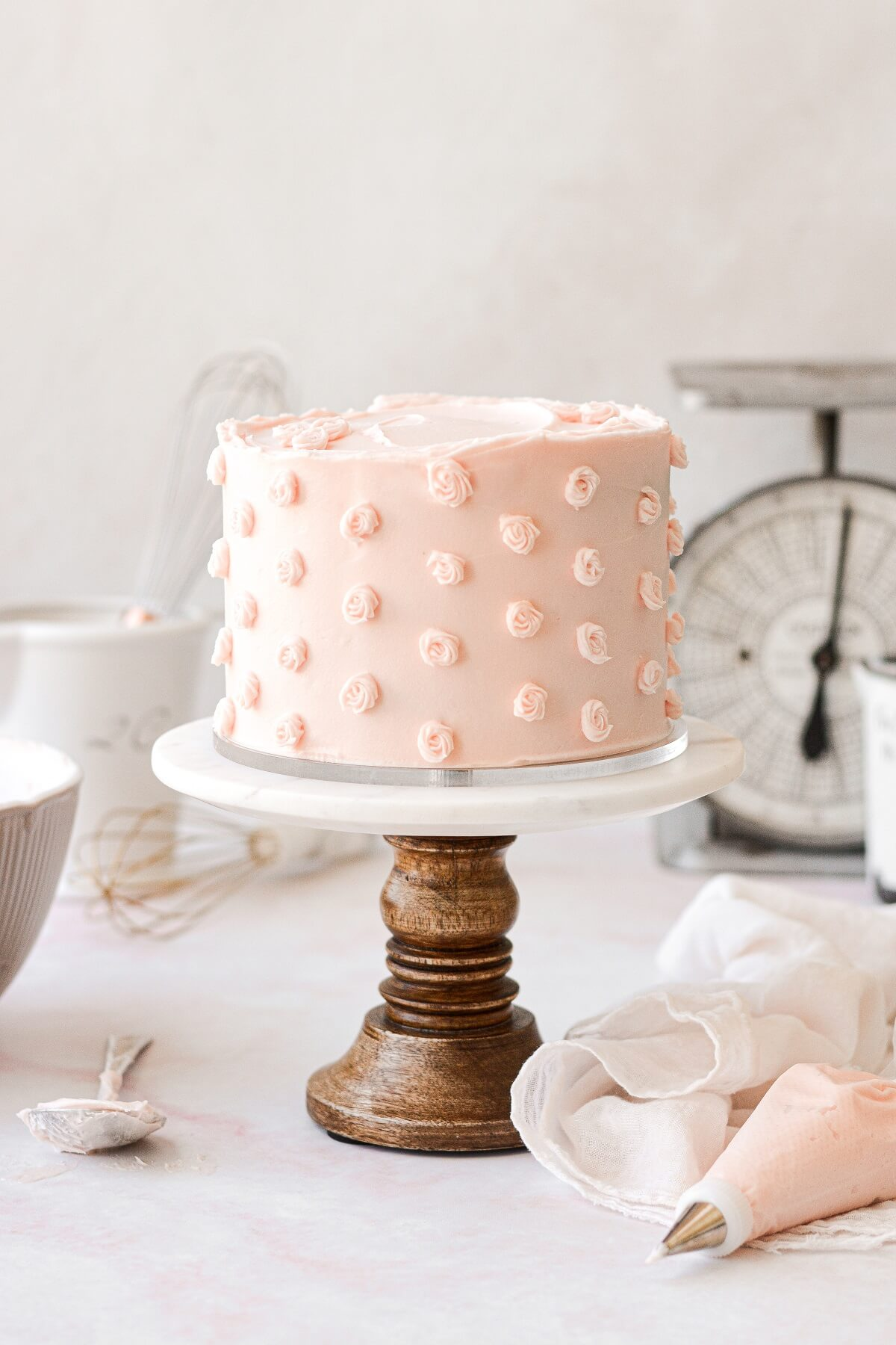 A pale pink frosted cake, with buttercream rosettes, on a marble and wood cake stand.