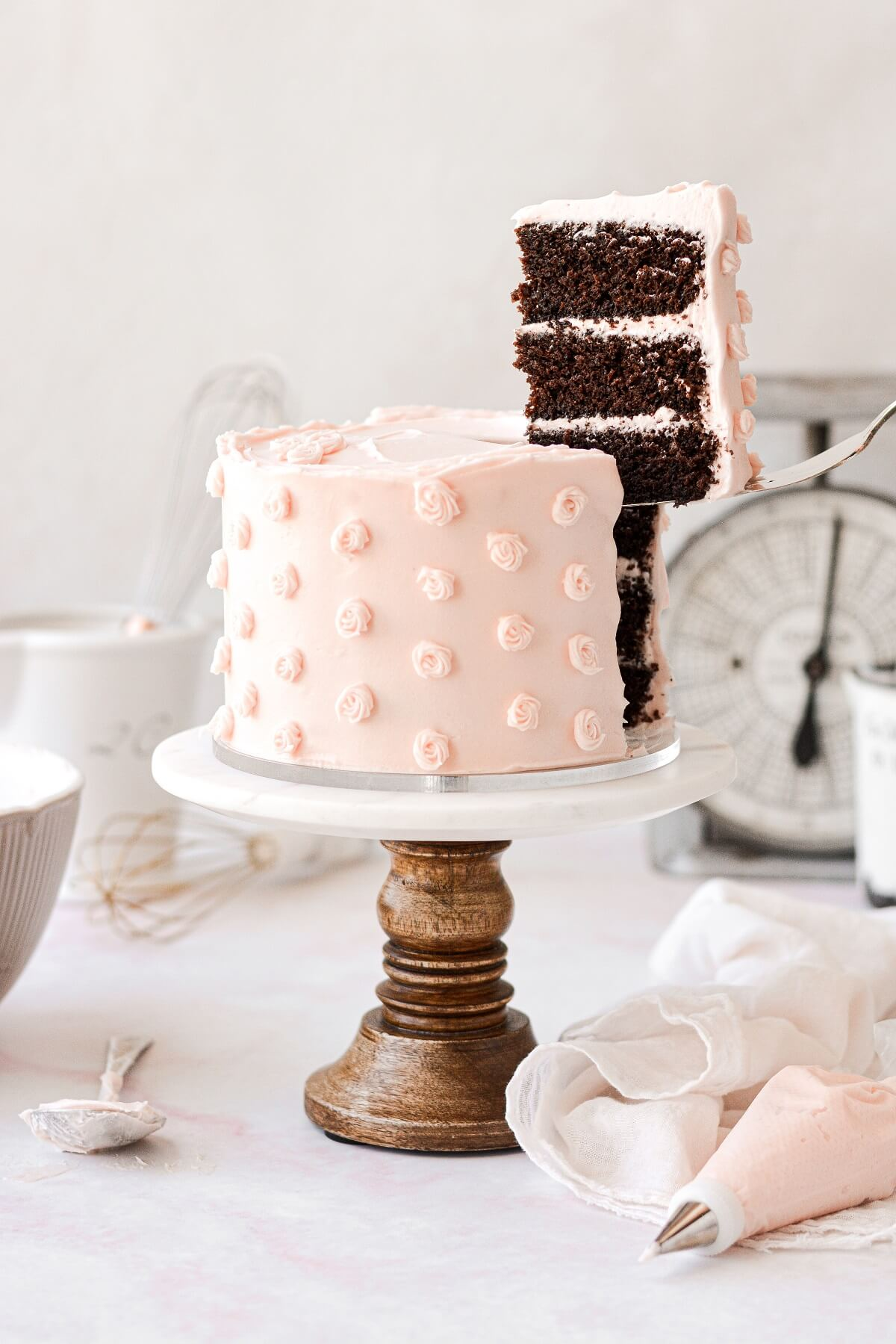 A slice of chocolate cake being lifted out of a layer cake.