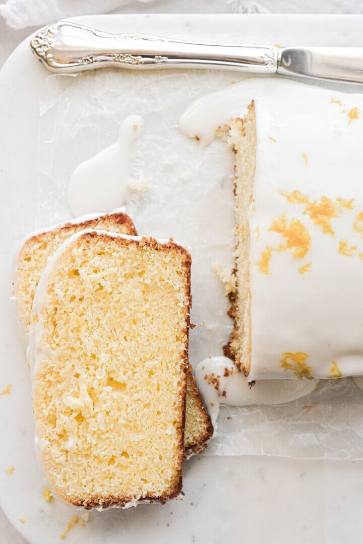 Slices of lemon loaf cake on a marble board.