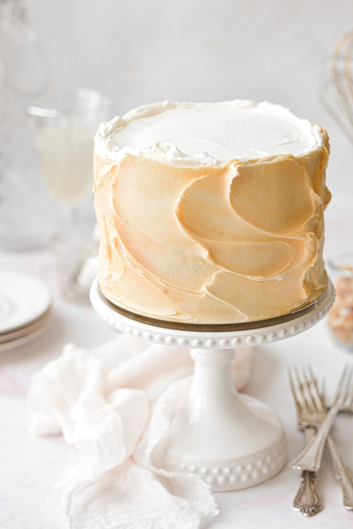 Mimosa cake on a white cake stand.