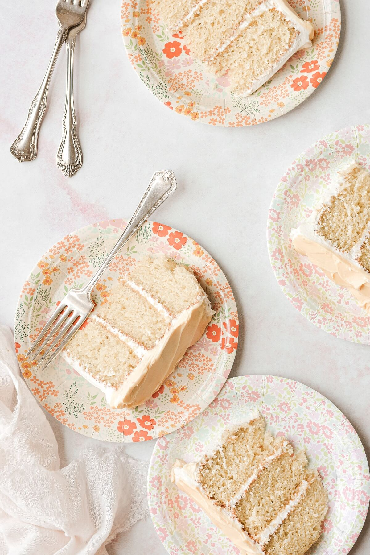 Slices of mimosa cake on flowered paper plates.