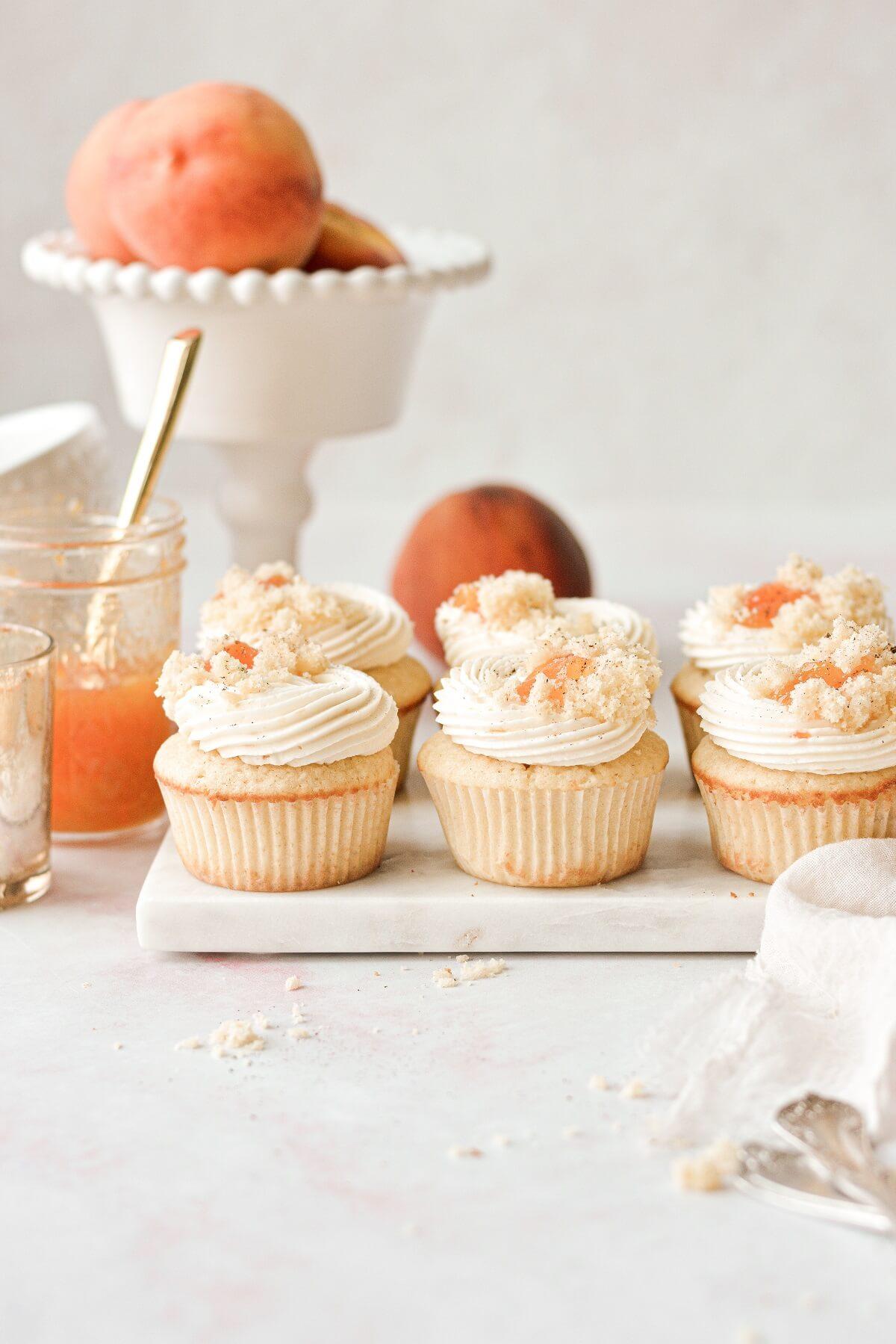 Peach cupcakes on a marble board.