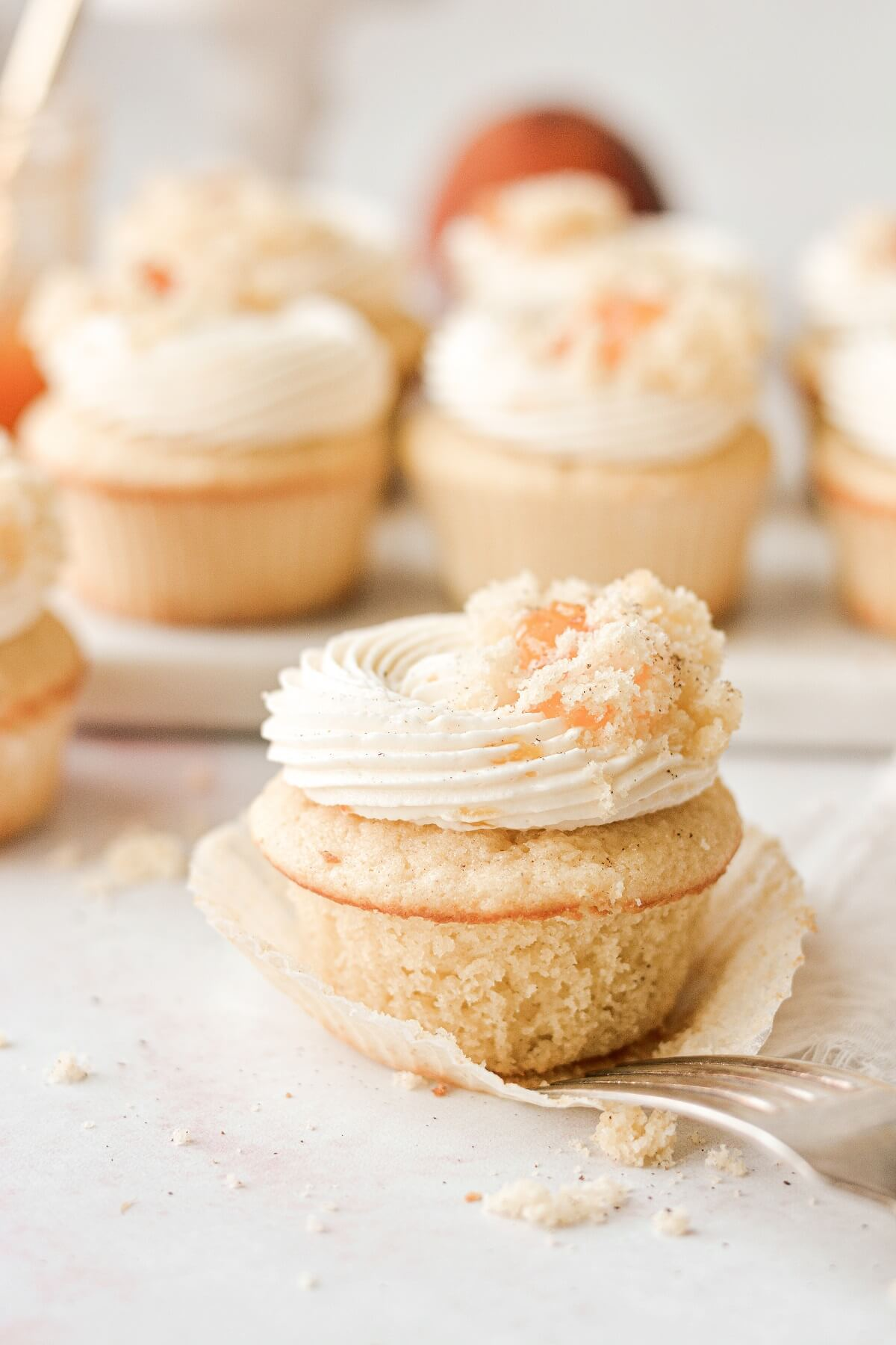 A peach cupcake with the wrapper opened.