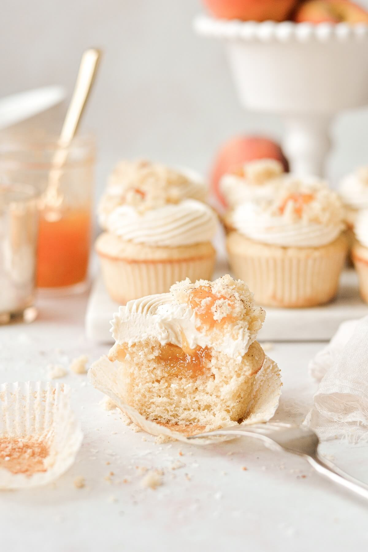 A peach cupcake with one bite taken.