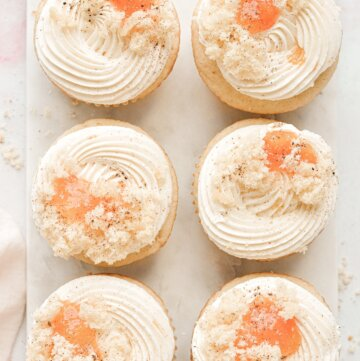 Peach cupcakes with swirls of buttercream and peach jam on top.