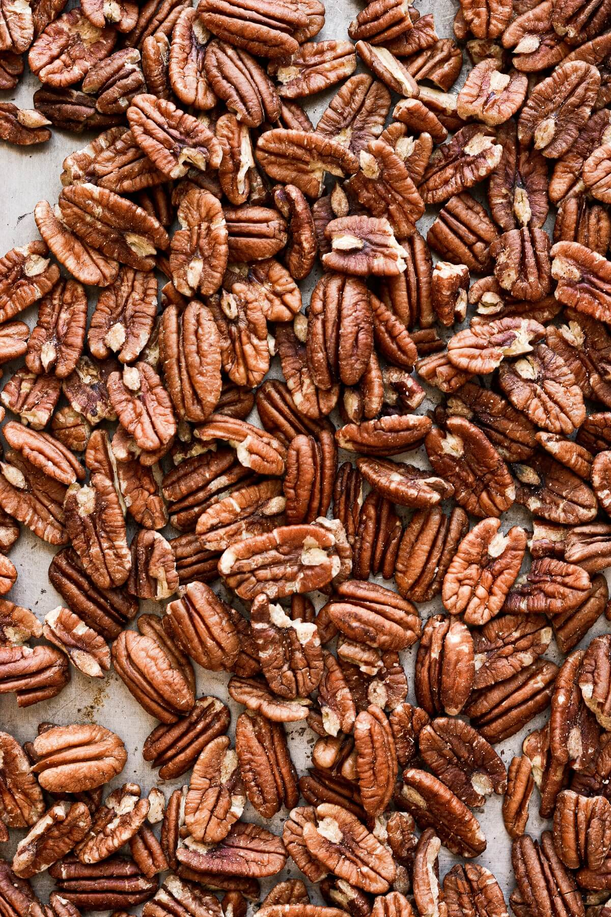 Pecans spread out on a baking sheet.