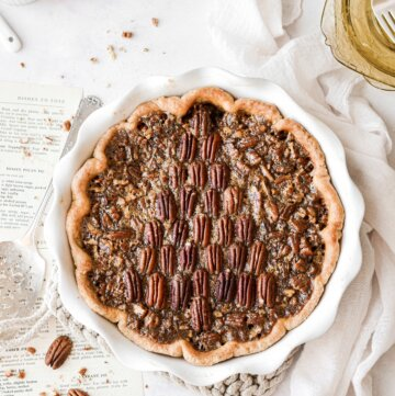 A pecan pie with pecans arranged like a Christmas tree on top of the pie.