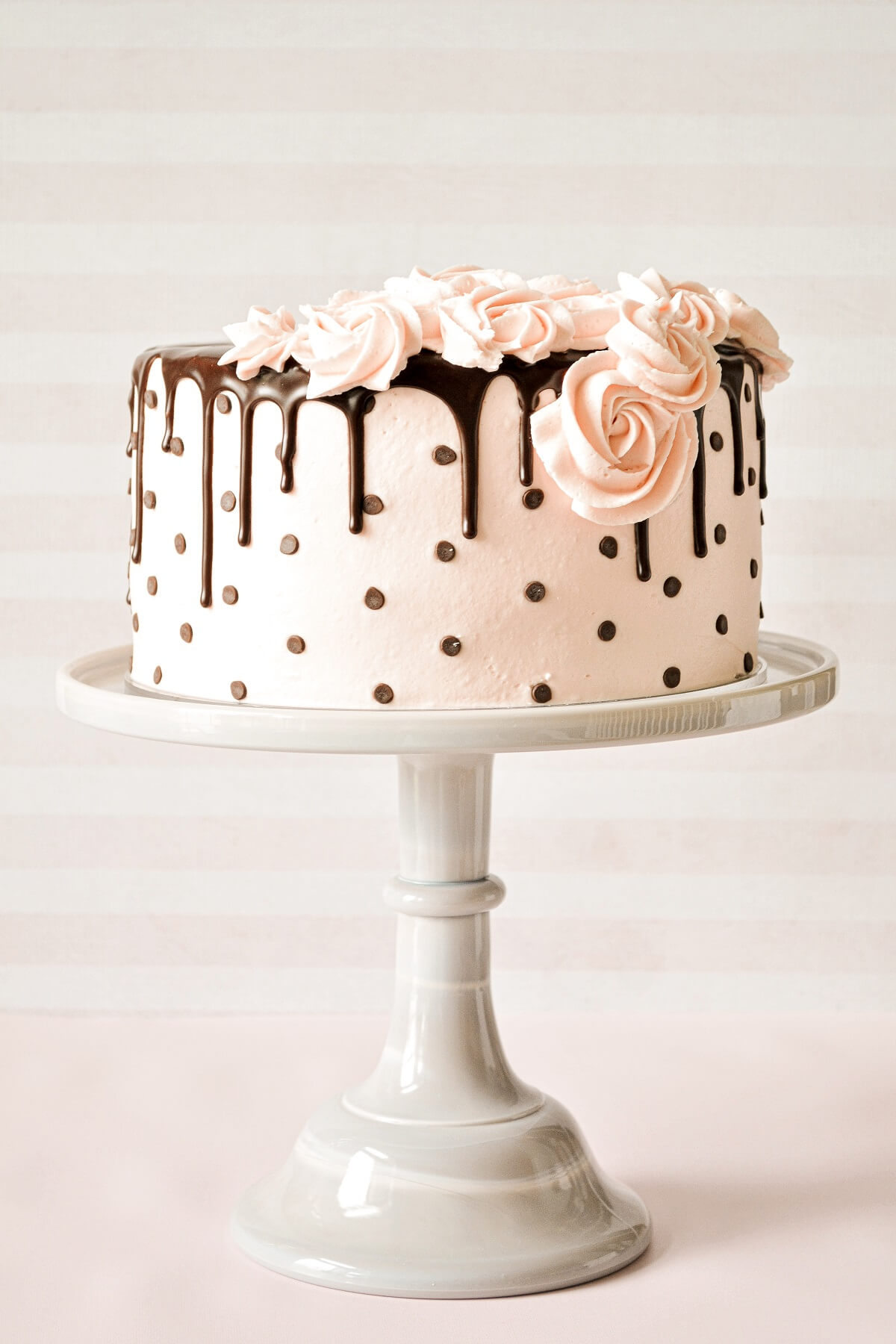 A polkadot drip cake with buttercream roses and chocolate ganache drip.