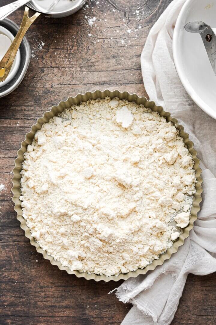 Shortbread dough crumbs in a tart pan.