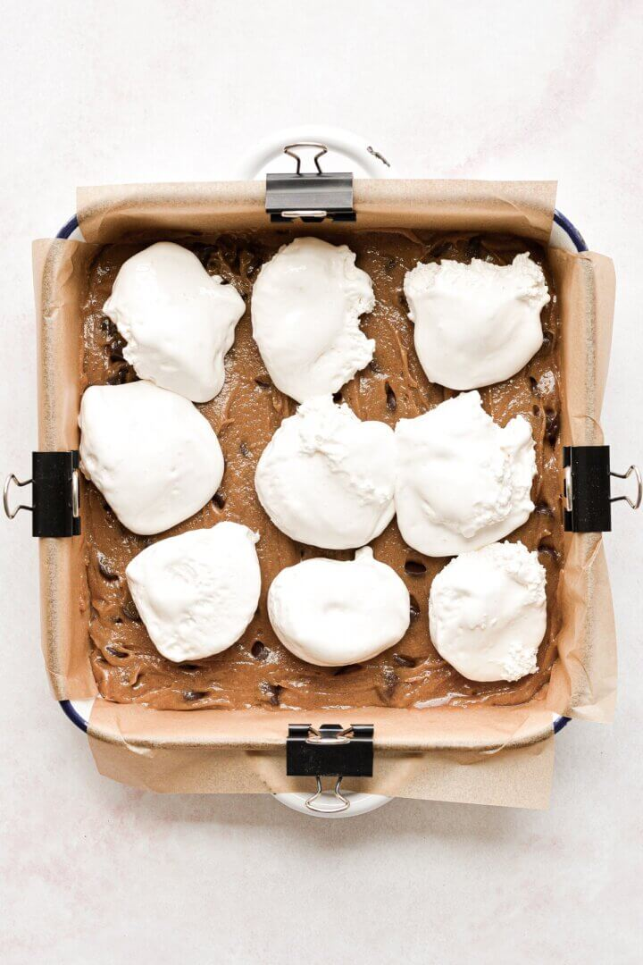 Cookie dough in a baking pan, topped with marshmallow fluff.