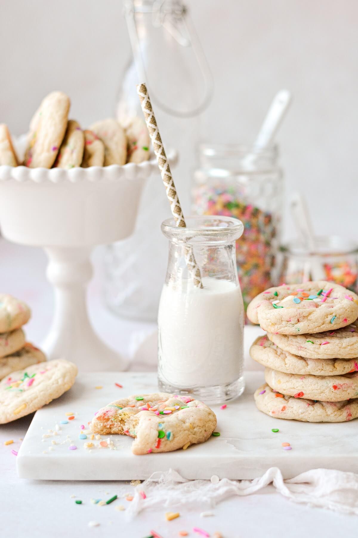Sprinkle cookies with a glass jar of milk.