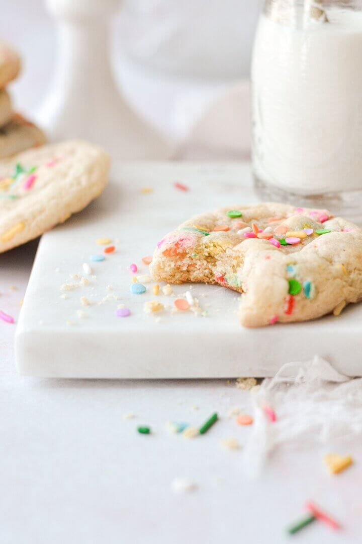 A sprinkle cookie with a bite taken.