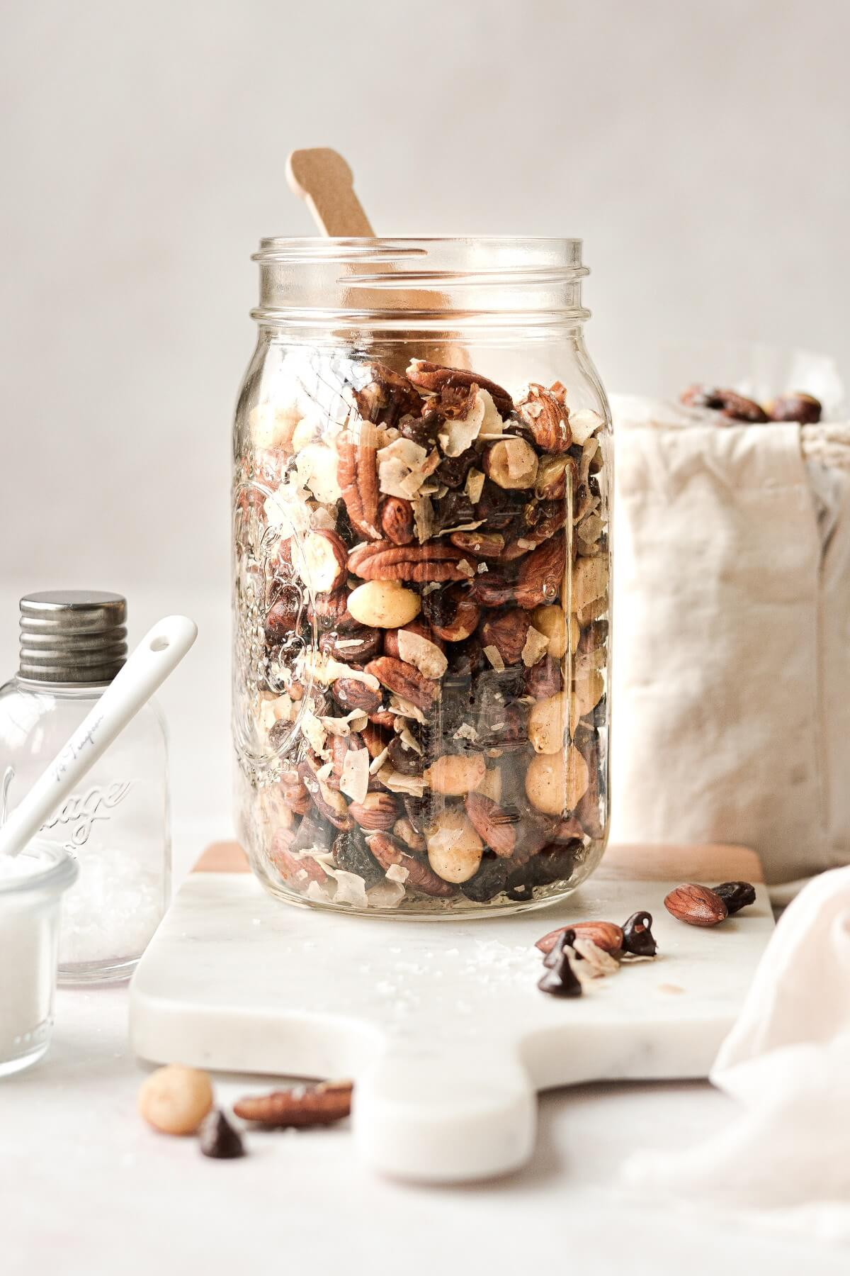 Homemade toasted trail mix in a glass jar.