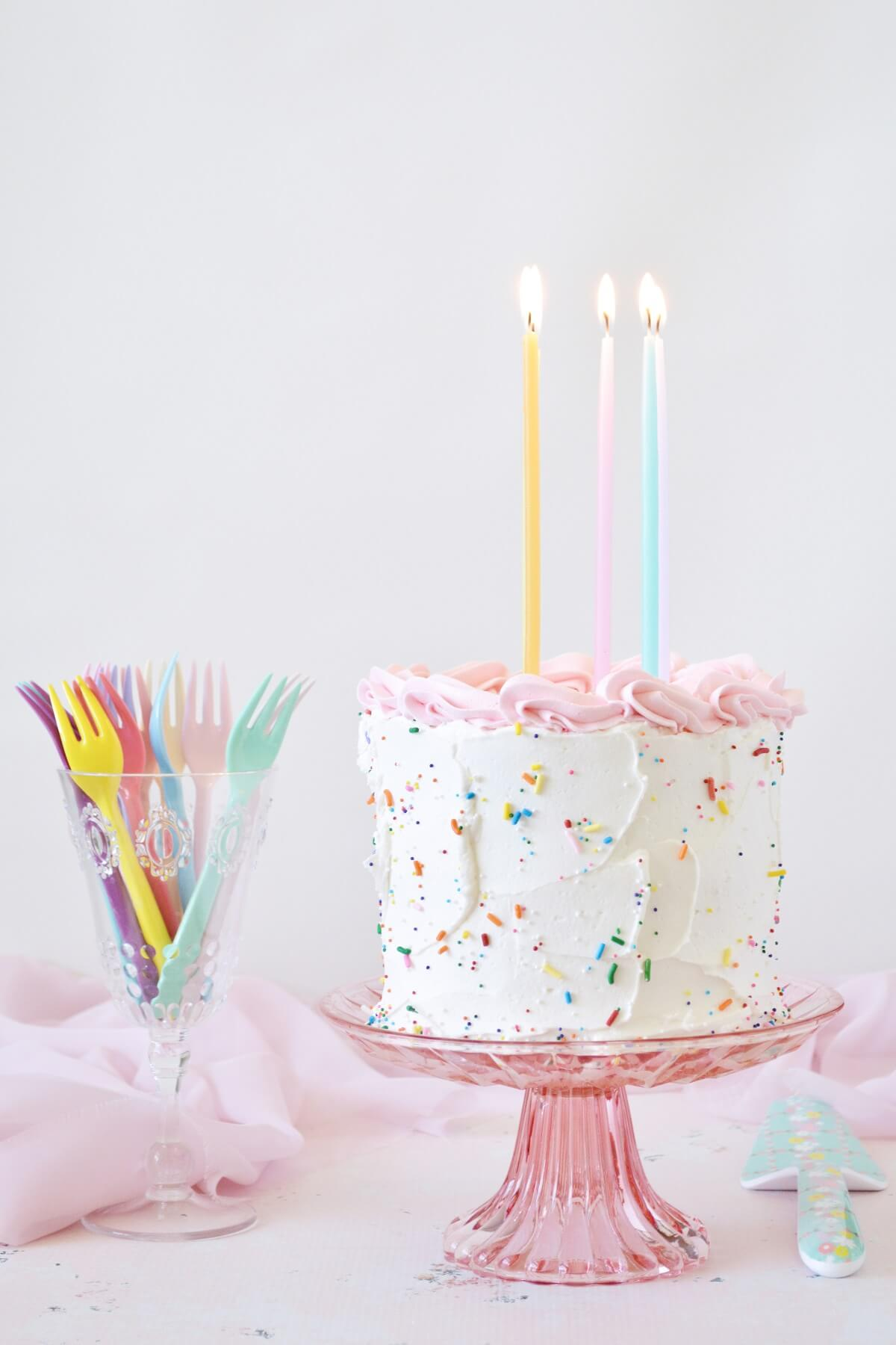 A birthday cake with sprinkles and candles.