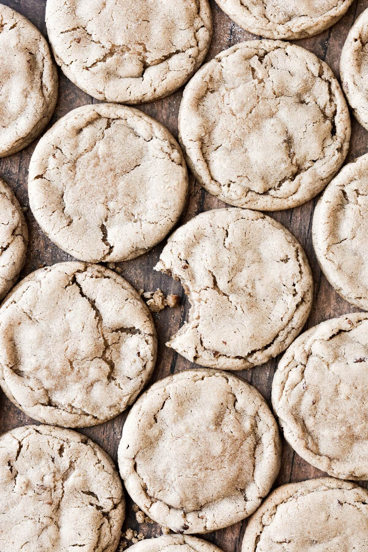 Appledoodles (apple cider cookies) on a wooden board, one with a bite taken.